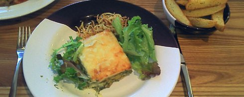 Courgette and spinach lasagne with shoestring chips and green leaves